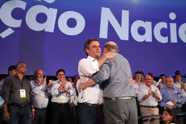 Aécio Neves abraça José Serra durante convenção; Carlos Mosconi ao fundo. Foto George Gianni